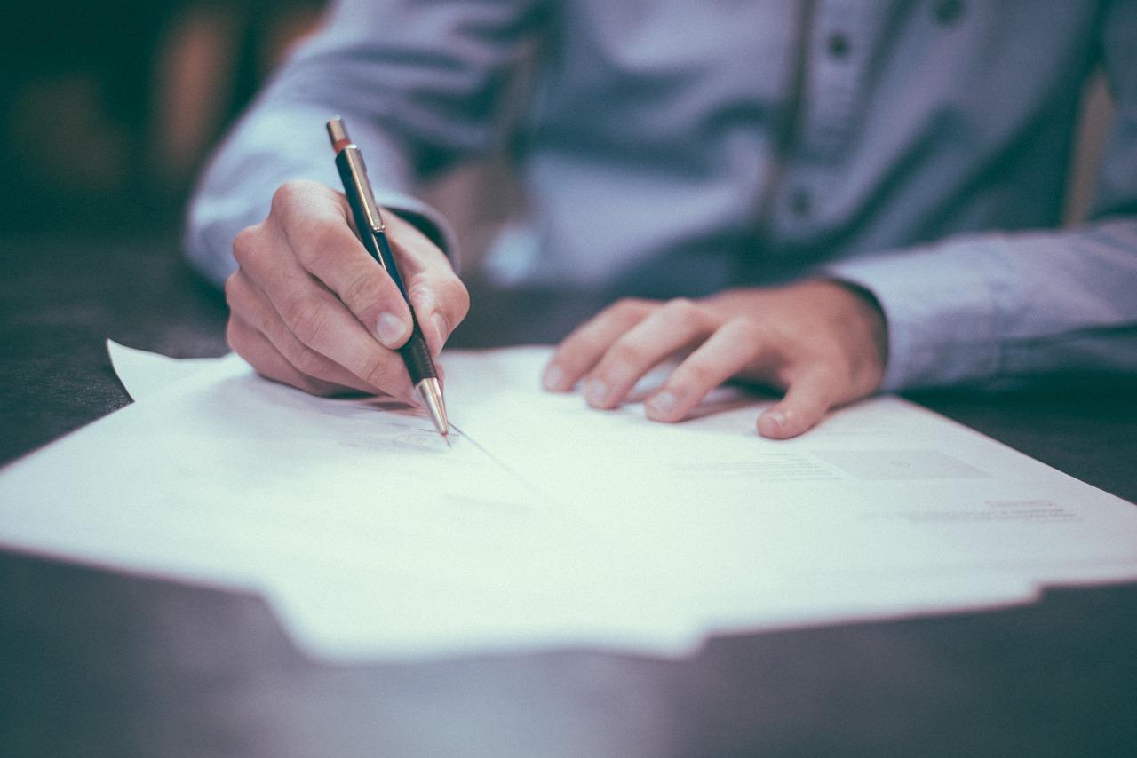 persona firmando documentos con una pluma